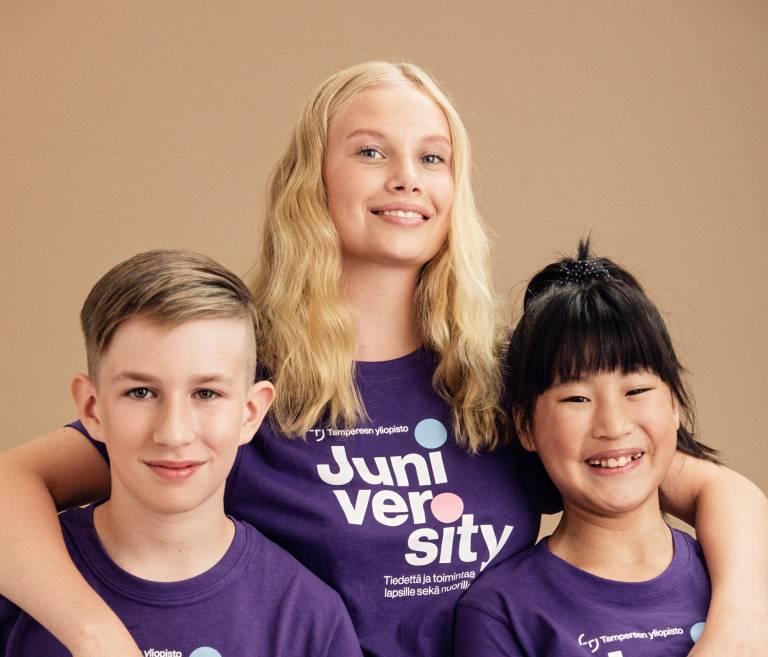 Valokuva, ryhmäkuva kahdesta hymyilevästä lapsesta nuoren kainalossa, kaikilla juniversityn paita päällä.