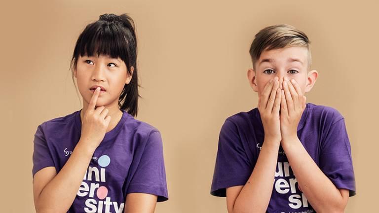 Valokuva, jossa kaksi mietteliästä lasta juniversityn paidoissa.