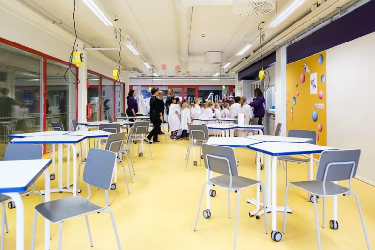 Valokuva juniversityn tiedeluokasta, taustalla oppilasryhmä työskentelemässä.