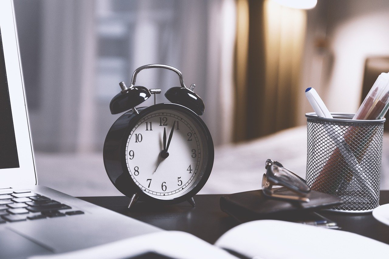 Kuvassa herätyskello kuvaamassa aikatauluja.