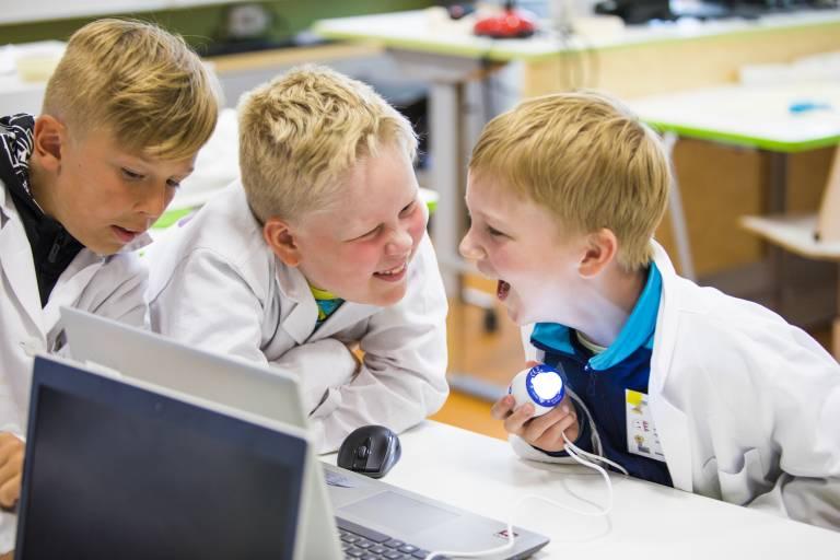 Valokuva, jossa kolme iloista lasta työskentelemässä yhdessä mikroskoopilla.