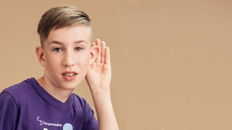 Valokuva lapsesta, joka pitää kättä korvansa takana, kuin kuullakseen paremmin.