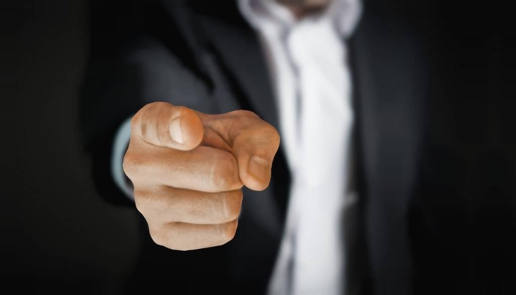 Mies osoittaa sormella katsojaa