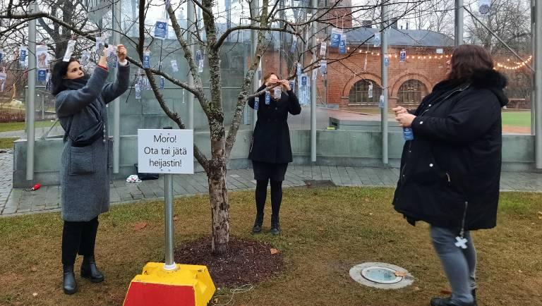 FabLabin tiimin Taru Arvio, Noora Nyberg ja Hanne Lehtola ripustavat heijastimia ohikulkijoiden mukaan otettaviksi Laikunlavalla.