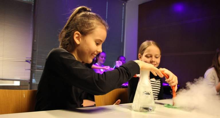 Valokuva, jossa kaksi lasta tekevät tiedekoetta kuivajäällä.