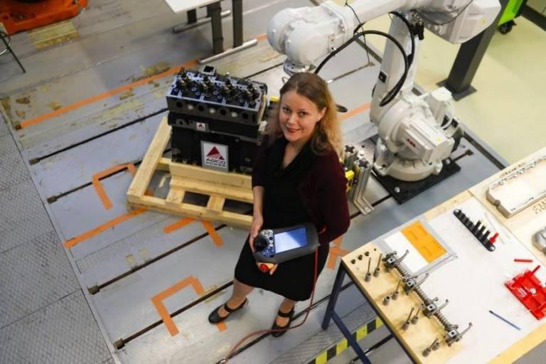 Hymyilevä nainen tekniikan laboratoriossa.