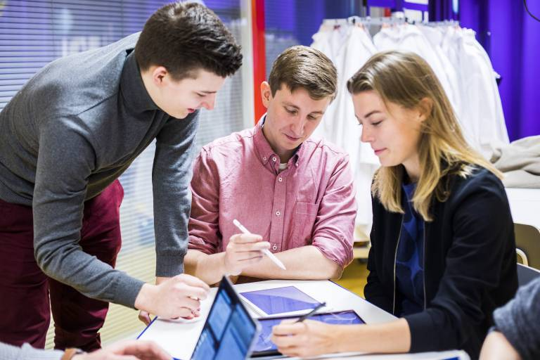 Valokuva, jossa kolme nuorta työskentelemässä yhdessä tablet-tietokoneilla