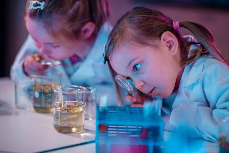 Valokuva. Kaksi lasta tutkimassa suurennuslasilla dekantterilasissa olevia nesteitä laboratoriotakit päällä.