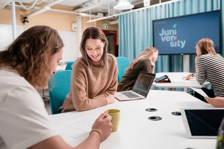 Valokuva. Opettajia keskustelemassa Juniversityn luokkatilassa.