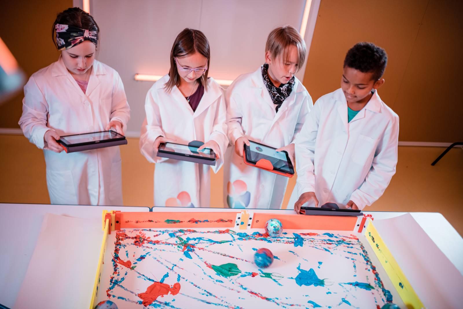 Valokuva, neljä lasta tekemässä robottipallomaalausta tablet-tietokoneilla.