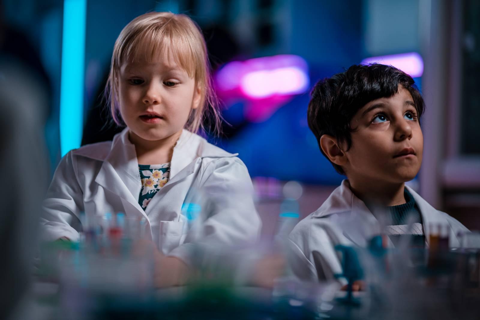 Valokuva, lähikuvassa kaksi pientä pohdiskelevaa lasta laboratoriotakit päällä.