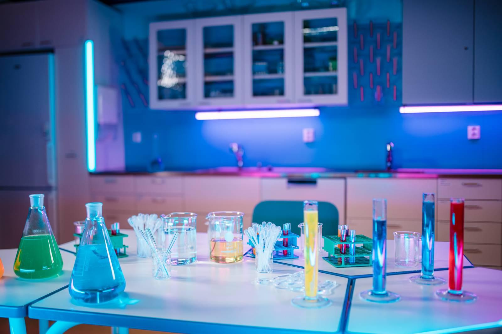 Valokuva juniversityn tiedeluokasta jossa taustalla laboratoriokeittiö ja etualalla pöytä, jossa värikkäitä liuoksia laboratorioastioissa.