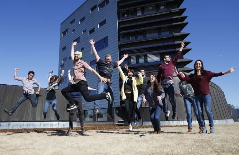 Valokuva, ryhmä nuoria hyppäämässä innokkaina ilmaan Tampereen yliopiston Hervannan kampuksen pihassa.