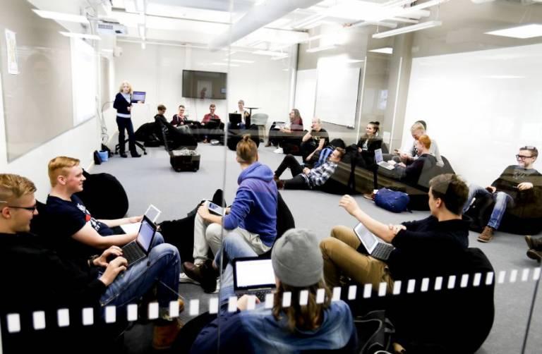 Valokuva, kuva luokkatilasta lasin läpi otettuna. Tilassa paljon nuoria opiskelemassa sekä luennoitsija.