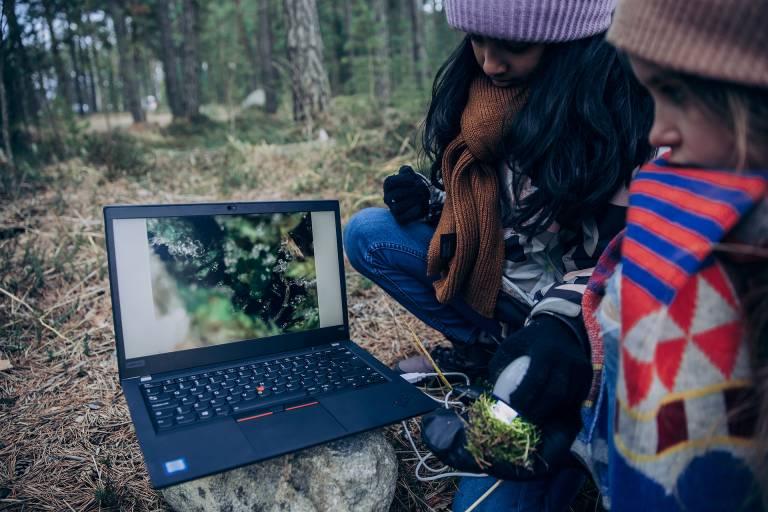Valokuva, kaksi lasta tutkimassa mikroskoopilla metsässä.