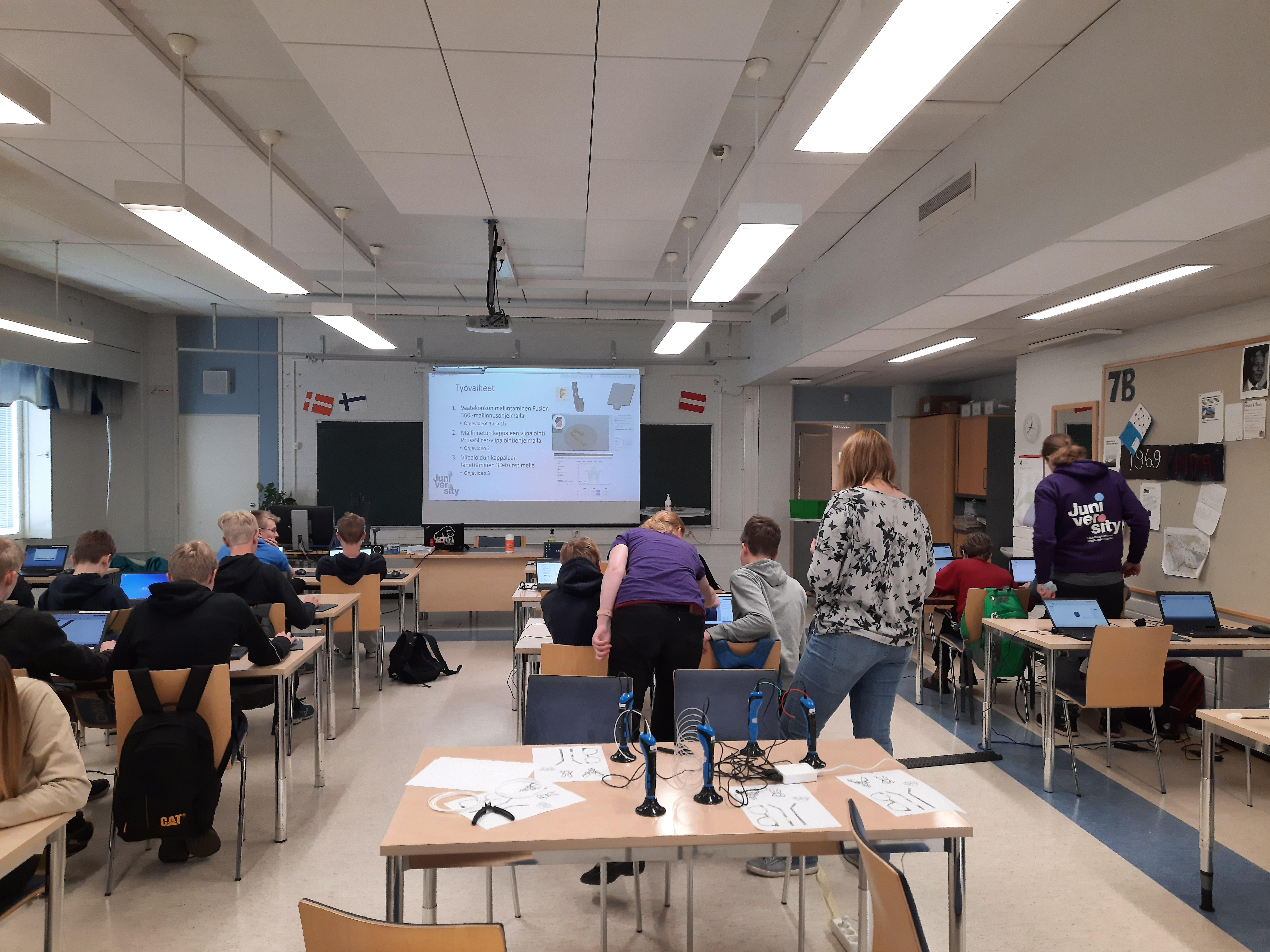 Valokuva, Juniversityn ohjaajia opastamassa yläokulun oppilasryhmää 3D-tulostukseen luokkatilassa.