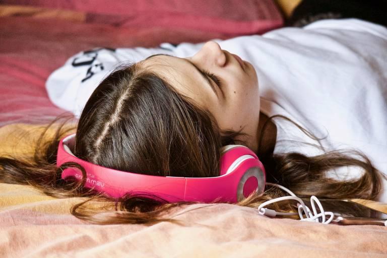 Valokuva, nuori makaamassa kädet pään takana ja kuulokkeet päässä.