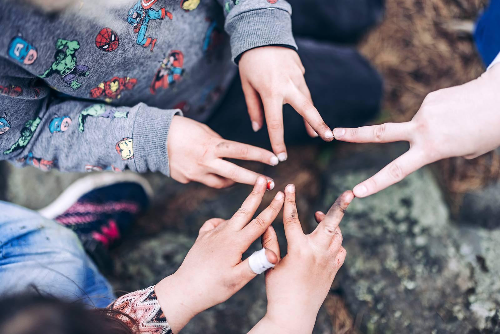 Valokuva, jossa useamman ihmisen sormet muodostavat tähtikuvion.