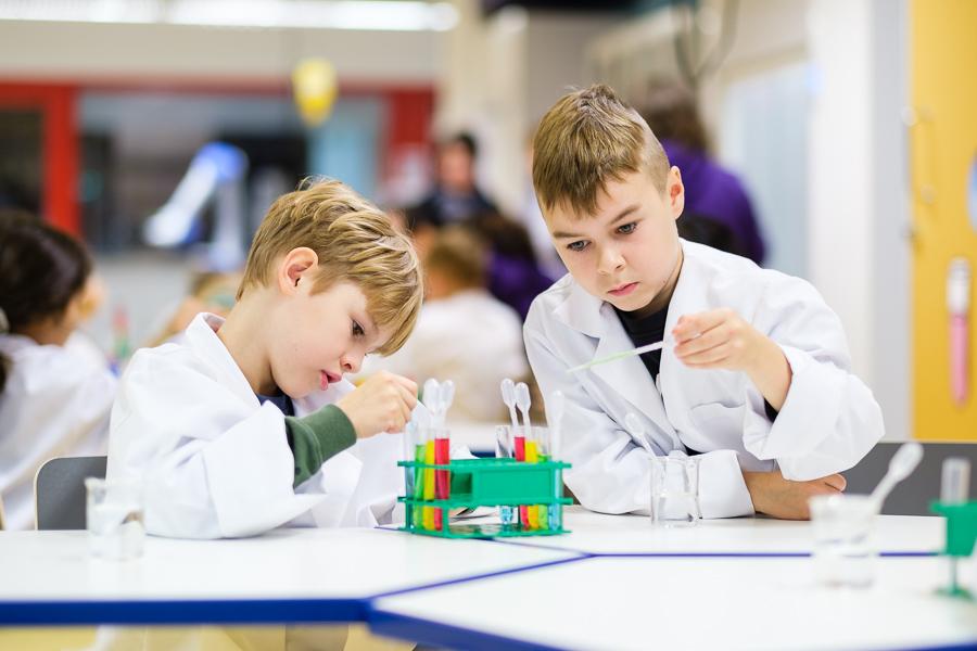 Kaksi lasta pipetoimassa värikkäitä nesteitä koeputkiin labroratoriotakit päällä.